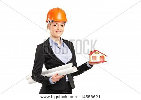 Smiling Forewoman Holding A Model House And Blueprints