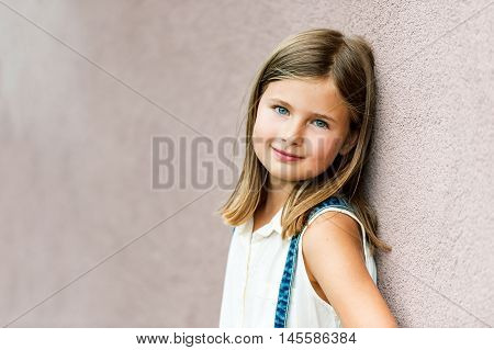 Close up portrait of a cute little girl of 7-8 years old leaning to pink wall
