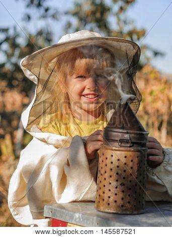 Little girl beekeeper blows smoker for bees.