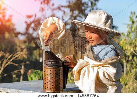 Little beekeeper blows smoker for bees. beekeeping