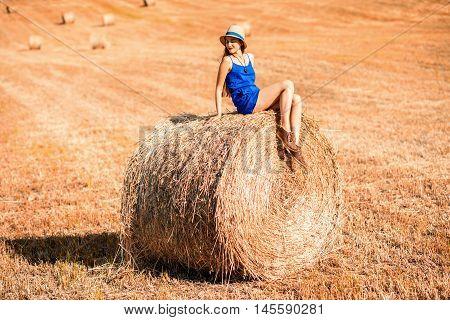 Young woman in blue dress enjoying nature on the hayfield in Tuscany in Italy