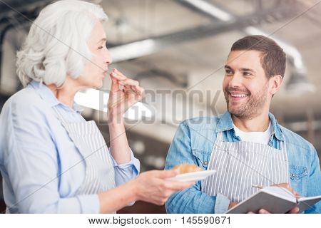 Tastes great. Positive delighted woman holding croissant and revealing the receipt while