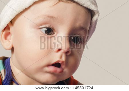 Portrait of a cute baby boy looking down.  Adorable six month old child wearing a hat.