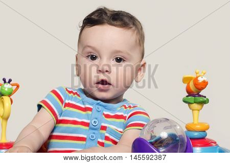 Cute baby boy sitting and playing with toys. Adorable six month old child happy looking surprised raising his eyebrow.