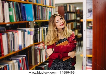 Female student choses a book in college library