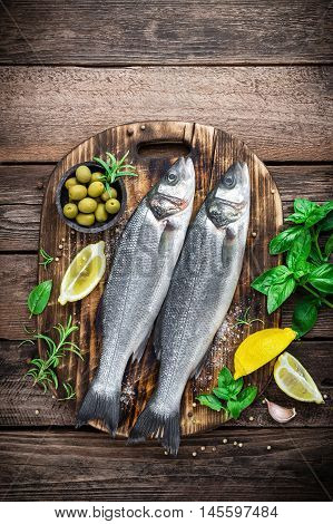 raw seabass fish on wooden background top view