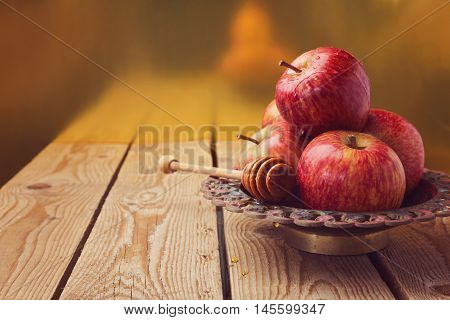 Apple and honey on wooden table for jewish Rosh hashana (new year) celebration