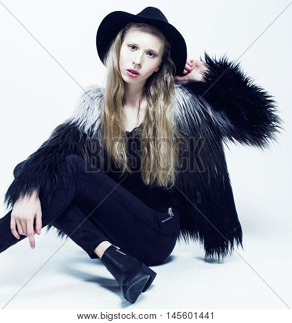 young blonde teenage hipster girl in hat and fur coat, fashion dressed model, studio shot