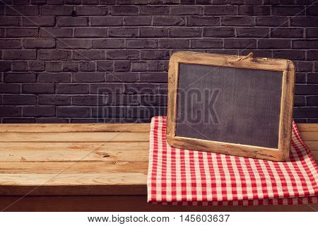 Chalkboard background with red checked tablecloth over black brick wall