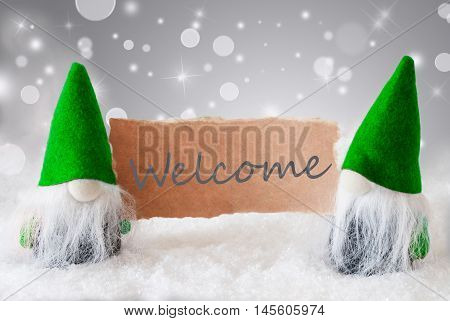 Christmas Greeting Card With Two Green Gnomes. Sparkling Bokeh And Noble Silver Background With Snow. English Text Welcome
