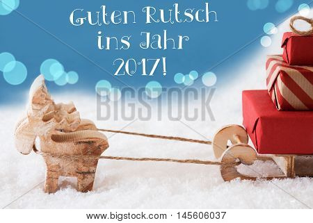 Moose Is Drawing A Sled With Red Gifts Or Presents In Snow. Christmas Card For Seasons Greetings. Light Blue Background With Bokeh Effect. German Text Guten Rutsch Ins Jahr 2017 Means Happy New Year