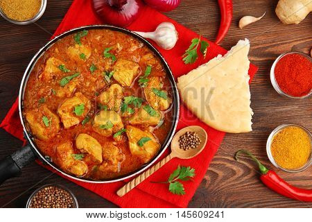 Tasty chicken curry in pan and spices on wooden background