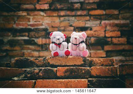 Toy teddy bear Brick wall background. Cute teddy bear