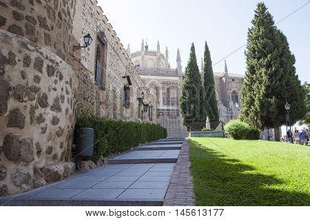 Toledo Spain - August 28 2016: Park with Monastery of San Juan de Los Reyes at bottom Toledo Spain