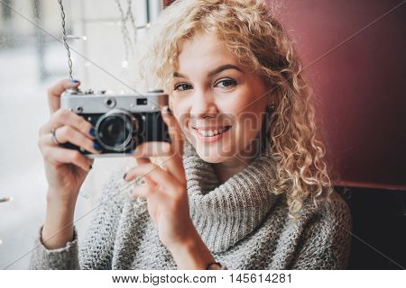 Young blond curly female in warm sweater with old film camera smiling and shooting a photo in the cafe, winter city outside the window