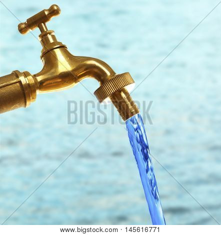 Conservation water concept. Faucet with stream on blue water surface background.