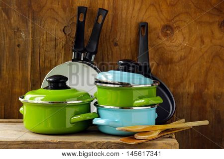 set of metal pots cookware on a wooden, domestic kitchen