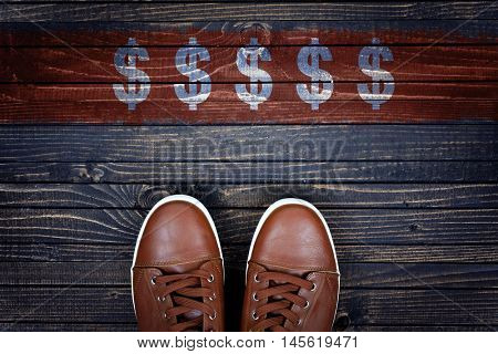 Dollar Sign message and sport shoes on wooden floor