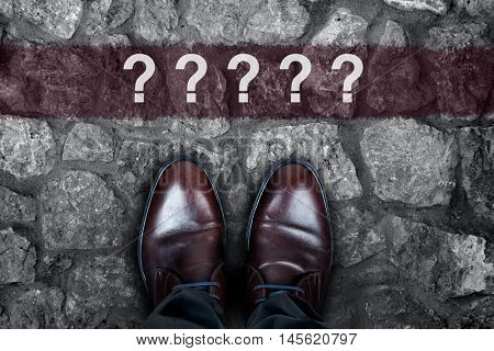 Question marks message on asphalt and business shoes