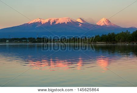 Sunset lighting Kluchevskaya group of volcanoes with reflection in the river Kamchatka.