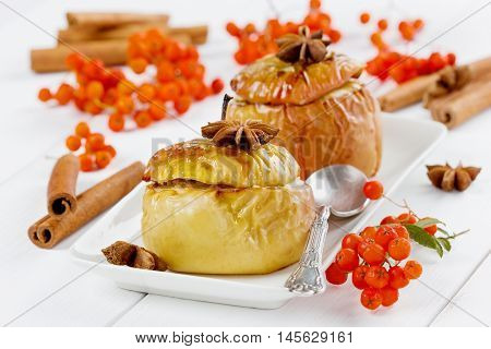 Baked apples with honey, raisins, curds and nuts in a white plate decorated ashberry, cinnamon sticks and anise stars on a wooden background.