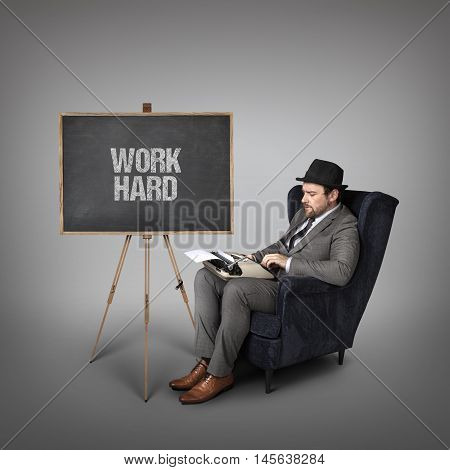 Work hard text on  blackboard with businessman and key