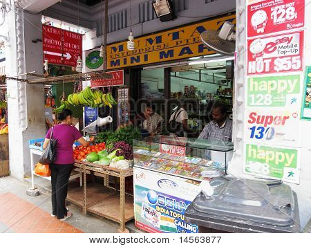 locals buying fruit and sim card stall in Little India