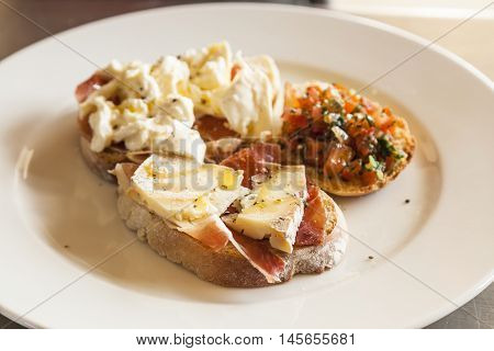 Bruschetta with prosciutto goat cheese and fried tomatoes