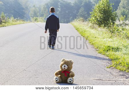 Boy goes away on the green field. Child leaves teddy bear on the road behind.Summer landscape with a boy.