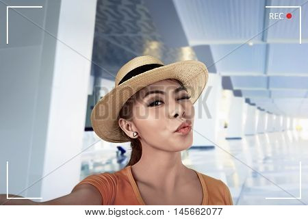 Young asian woman pose selfie in airport lobby with duckface expression and wearing hat