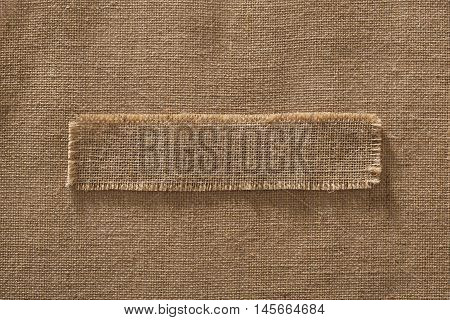 Burlap Fabric Frame Piece Label over Sack Cloth Linen Hessian Brown Background