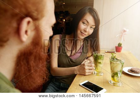 Old Friends Sitting Opposite One Another At Cozy Restaurant At Table Near Window, Having Fresh Drink