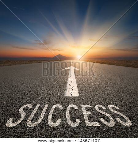 Driving on an empty road towards the big sunbeams and setting sun with sign on asphalt as text. Concept for success and passing time.