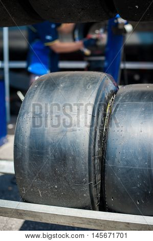 Motorsport slick tire close up with blurred man working in background