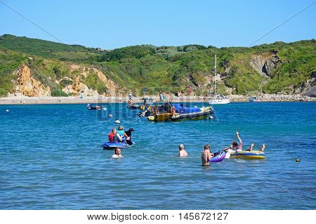 LULWORTH COVE, UNITED KINGDOM - JULY 19, 2016 - Holidaymakers relaxing in the sea with the beach to the rear Lulworth Cove Dorset England UK Western Europe, July 19, 2016.