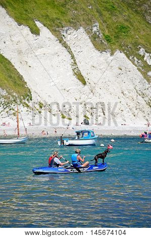 LULWORTH COVE, UNITED KINGDOM - JULY 19, 2016 - Holidaymakers and their dog in an inflatable boat with the beach to the rear Lulworth Cove Dorset England UK Western Europe, July 19, 2016.