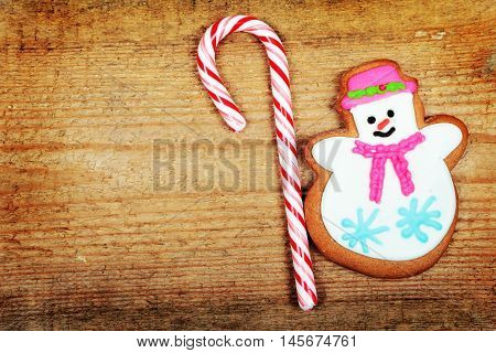 Christmas gingerbread snowman on old wooden background