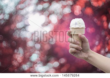 a woman hand holding Ice cream cone with abstract bokeh background,filtered image,colorful picture style