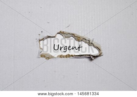 The word urgent appearing behind torn paper