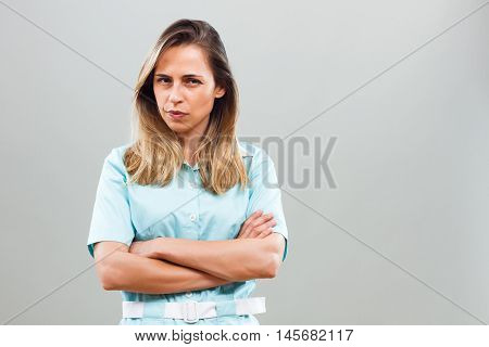 Beautiful angry nurse thinking about something and looking at camera.