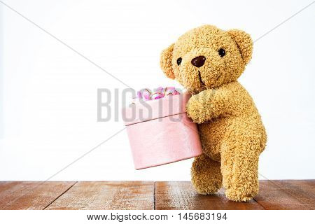 Teddy Bear Holding Gift Box On Wood
