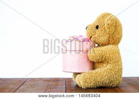 Teddy Bear Holding Gift Box On Wood