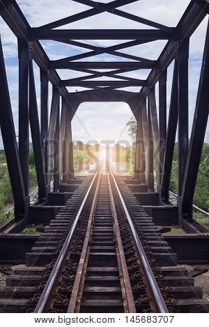 the length of railway with old steel bridge, filtered image,light effect added,selective focus,mean
