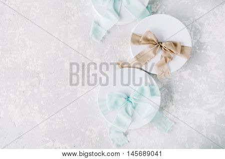 white gift cardboard box with brown and blue bow on concrete background. flat lat top view