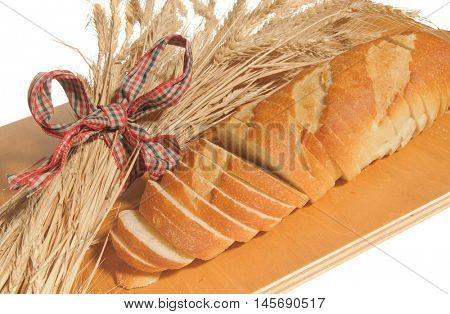Loaf of Sliced French Bread with wheat sheaves on a cutting board and isolated