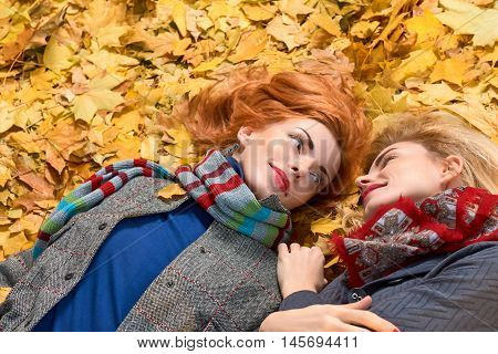 Fall Fashion. Woman in Stylish Autumn Outfit Having Fun. Sisters Best Friends Model in fashion knitted autumn clothes. Fall leaves around. Girl Relax Enjoy nature. Autumn fashion outdoor background