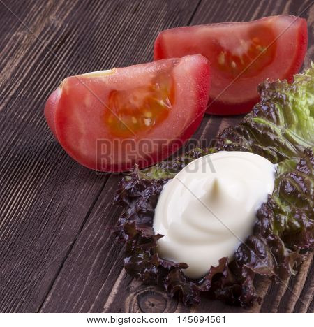 Slice Of Tomato. Handful Of Mayonnaise Swirl On Green Leaf