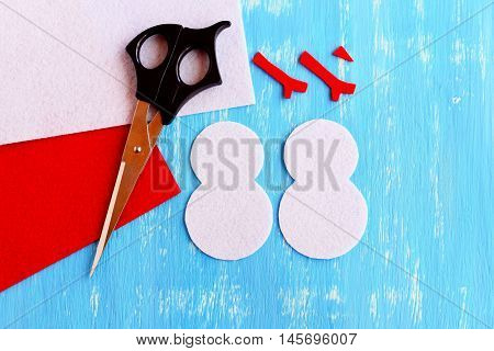 How to make a Christmas snowman decor. Step. Cut felt parts to create a Christmas tree decor. Snowman patterns, scissors, red and white felt sheets on wooden background. Christmas diy idea. Top view