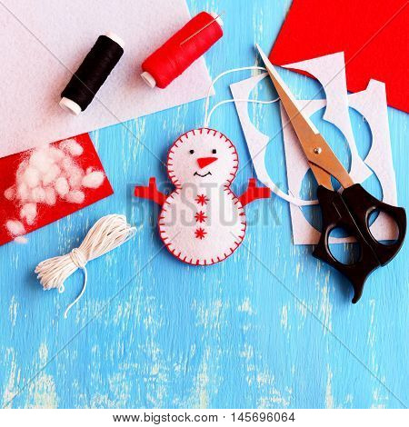 Cute felt Christmas snowman ornament, scissors, thread, needle, cord, felt sheets and scraps on wooden background. Supplies for making handmade snowman. Christmas kids crafts idea. Top view