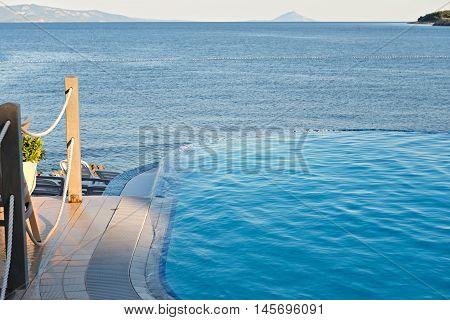 Empty infinity pool on the sunset, quiet bue sea